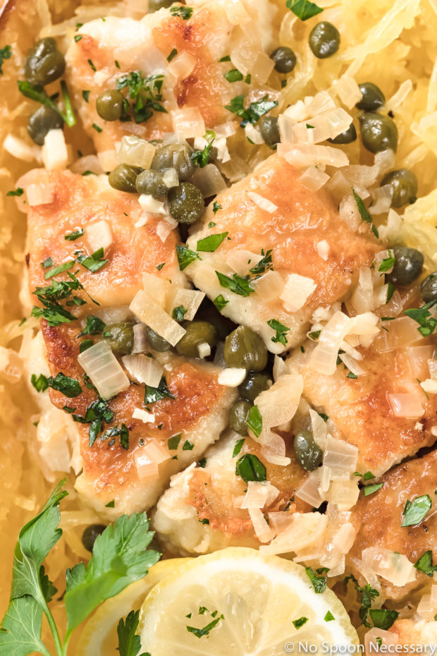 Overhead, up close shot of Healthy Chicken Piccata Spaghetti Squash Boats garnished with shredded parmesan, a slice of lemon and sprig of fresh parsley.