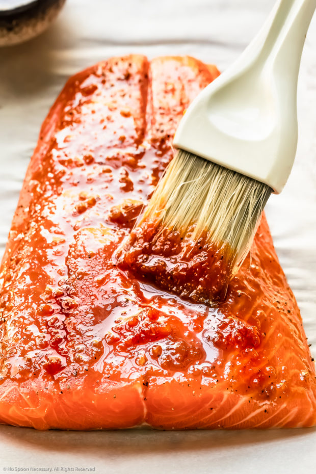 Angled photo of honey sriracha sauce being brushed on a large center-cut filet of salmon. (Photo of step 3 of the recipe.)