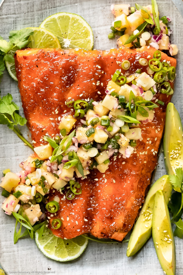 Overhead close-up photo of Baked Sriracha Salmon topped with sesame seeds, cilantro and tropical pineapple salsa on a gray serving platter.