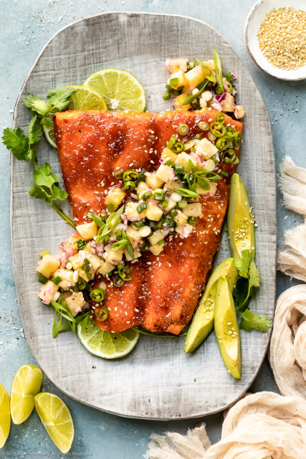 Overhead photo of Baked Honey Sriracha Salmon topped with tropical pineapple salsa on a gray serving platter with fresh lime wedges, a ramekin of sesame seeds and a pale tan napkin next to the platter.