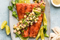 Overhead photo of Baked Honey Sriracha Spicy Salmon topped with tropical pineapple salsa on a gray serving platter with fresh lime wedges and a ramekin of sesame seeds next to the platter.