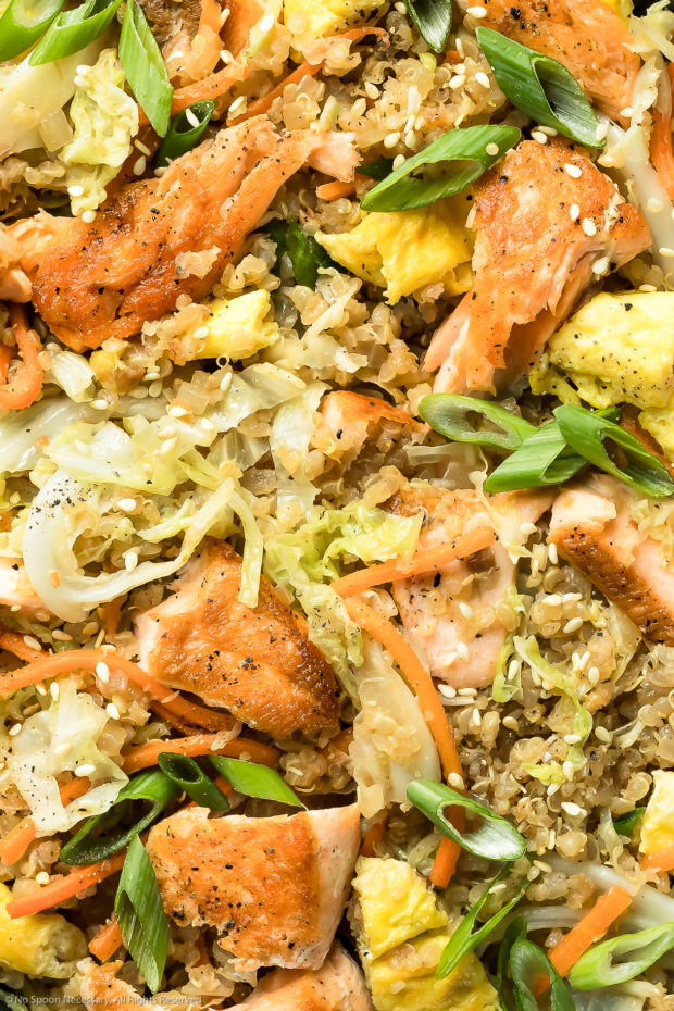Overhead, up close photo of Salmon Quinoa Fried Rice garnished with sliced scallions and sesame seeds.