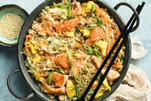 Overhead, landscape photo of Salmon Quinoa Fried Rice in a metal wok with a pair of chopsticks resting on the side of the wok and a ramekin of sesame seeds and pale tan napkin next to the wok.
