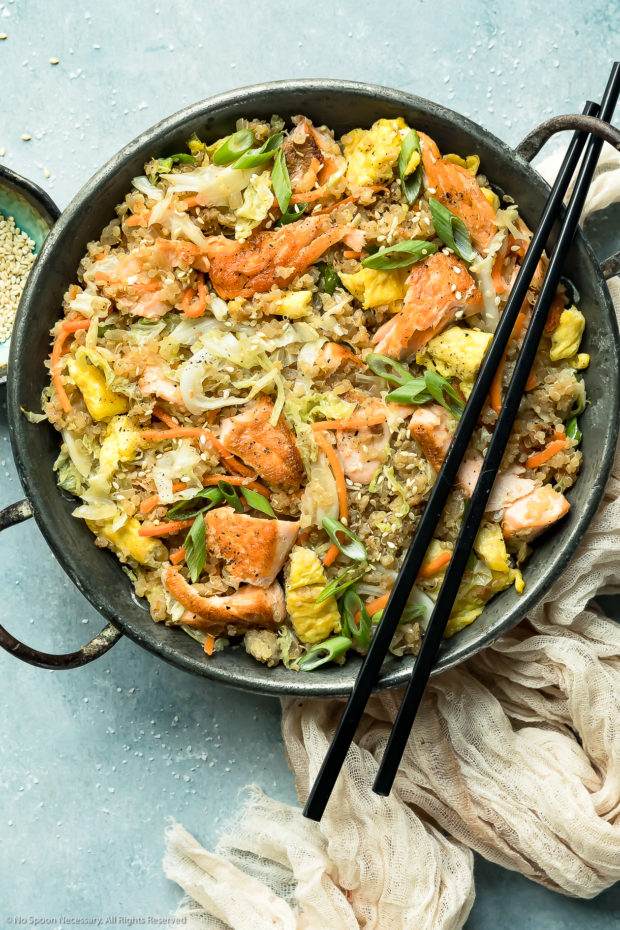 Overhead photo of Salmon Quinoa Fried Rice in a metal wok with a pair of chopsticks resting on the side of the wok and a ramekin of sesame seeds and pale tan napkin next to the wok.