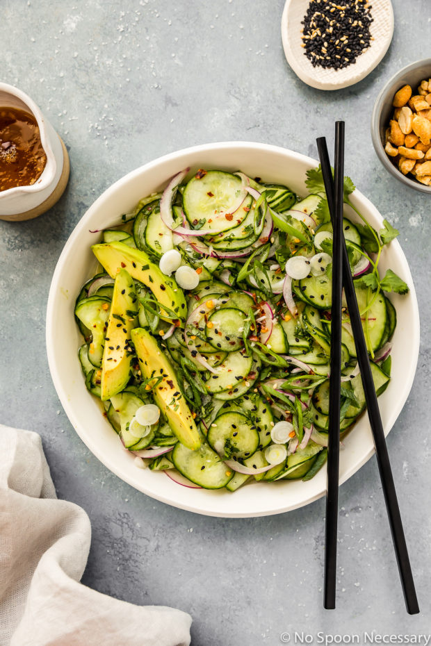 Overhead shot of Easy Asian Cucumber Salad in a white bowl with black chopsticks resting on the side of the bowl with a jar of dressing, neutral linen and ramekins of sesame seeds and peanuts surrounding the bowl.
