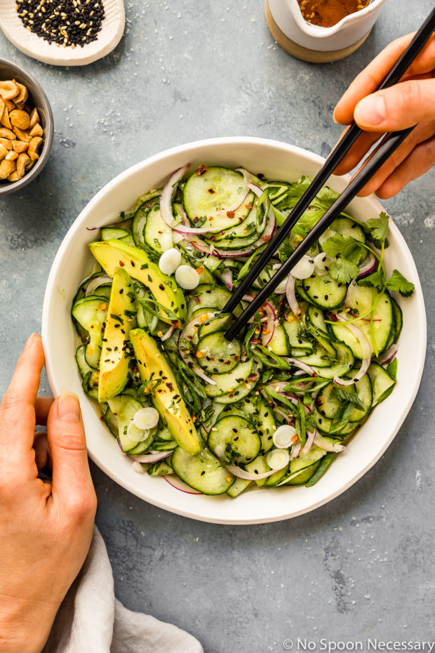 Overhead shot of Easy Asian Cucumber Salad in a white bowl with a hand holding the bowl and another hand holding black chopsticks inserted into the salad and a jar of dressing and ramekins of sesame seeds and peanuts surrounding the bowl.