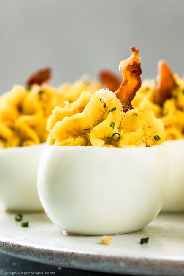 Straight on, up-close photo of Cheddar Bacon Deviled Eggs garnished with a slice of bacon and snipped chives on a white plate with a ramekin of snipped chives and crispy panko arranged around the plate.