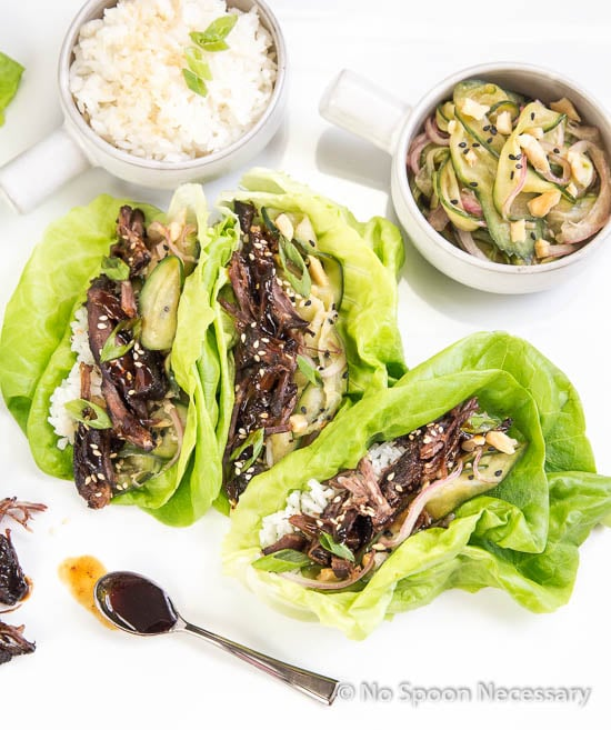 Overhead shot of three lettuce wraps filled with slow cooked Korean beef and cucumber noodles; small bowls of rice and cucumber salad in the background