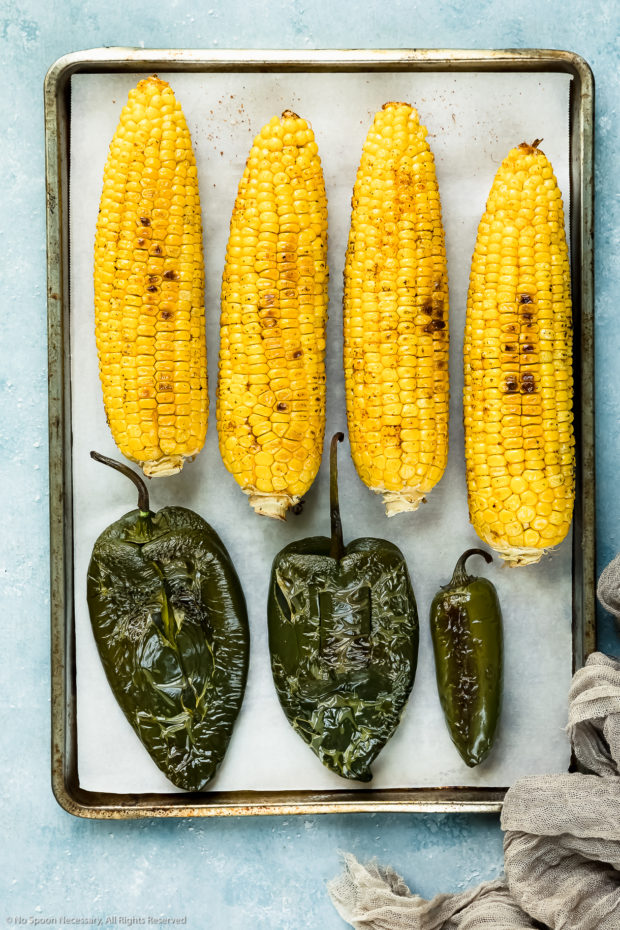 Overhead photo of a parchment paper lined sheet pan topped with roasted ears of corn, poblano peppers and a jalapeno pepper - photo of steps 4 and 5 of the sweet corn salsa recipe.
