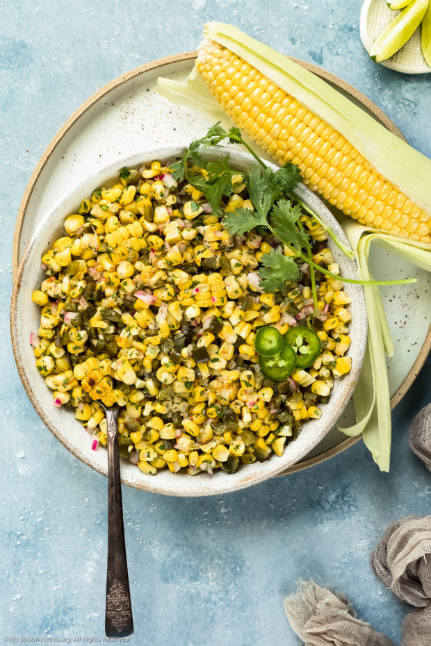 Overhead photo of Roasted Sweet Corn Salsa in a large white bowl with a spoon inserted into the salsa and an ear of corn and lime wedges next to the bowl.