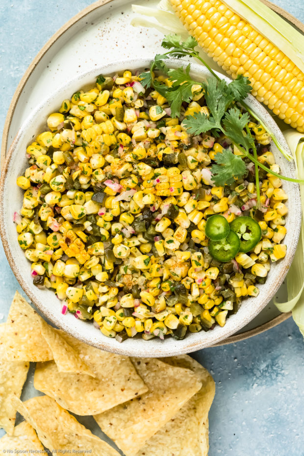 Overhead photo of Roasted Sweet Corn Salsa garnished with fresh cilantro in a large white bowl with an ear of corn and tortilla chips next to the bowl.