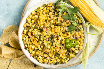 Overhead, landscape photo of Roasted Sweet Corn Salsa garnished with fresh cilantro in a large white bowl with an ear of corn and tortilla chips next to the bowl.