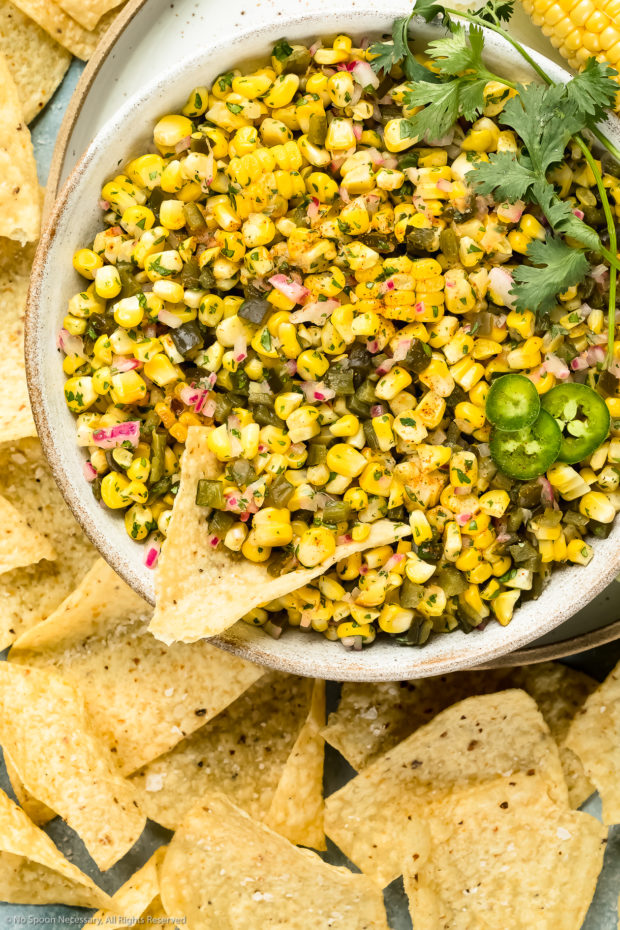 Overhead photo of Roasted Sweet Corn Salsa a large white bowl with a tortilla chip inserted into the salsa and more chips surrounding the bowl - photo of how to serve corn salsa as an appetizer.