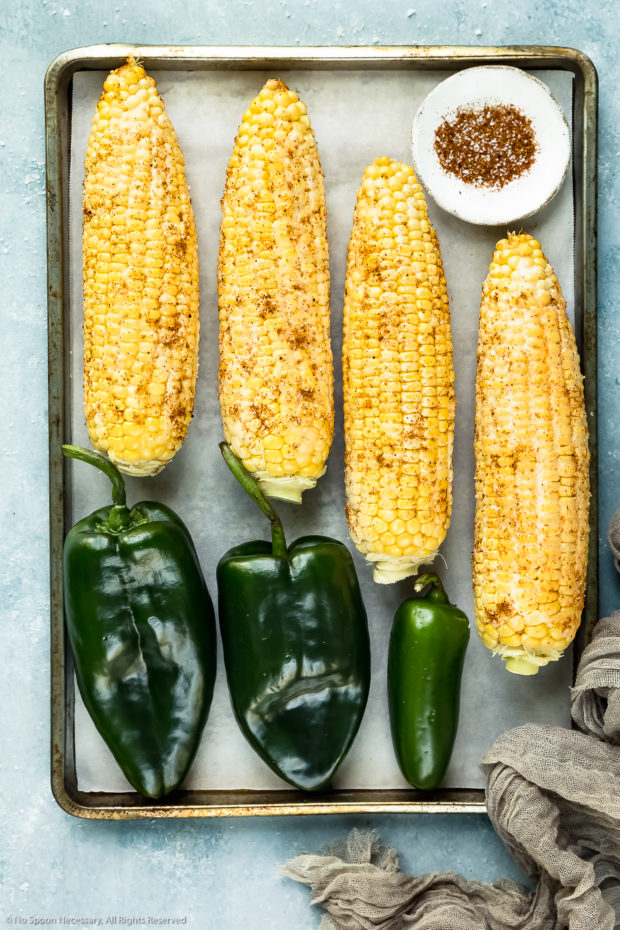 Overhead photo of a parchment paper lined sheet pan topped with two poblano peppers, a jalapeno pepper, and four buttered and seasoned ears of corn - photo of step 3 of the sweet corn salsa recipe.