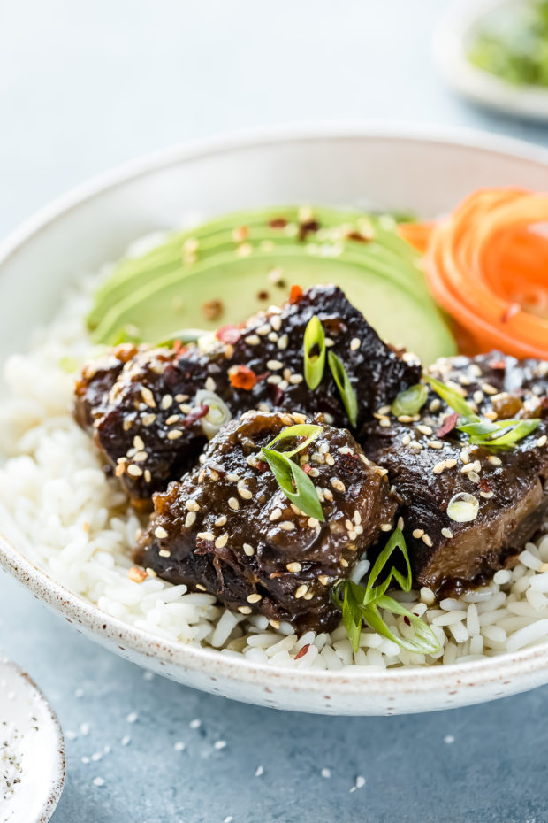 Angled shot of Slow Cooker Korean Short Ribs garnished with sesame seeds and scallions on a bed of rice with sliced avocado and carrot ribbons in a white bowl with ramekins of salt and sliced scallions arranged around the bowl.