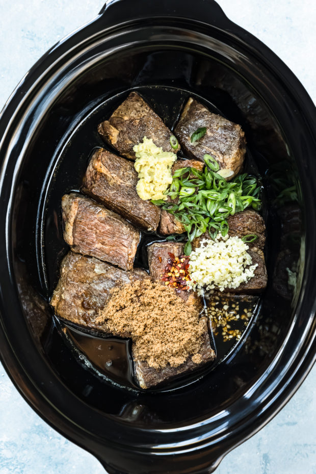 Overhead shot of a black slow cooker filled with seared short ribs, brown sugar, garlic, ginger, scallions, red pepper flakes and Korean short rib sauce - photo of step 3 of the slow cooker Korean short ribs recipe.