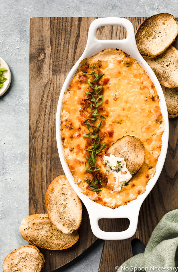 Overhead shot of Hot Cheesy Bacon Broccoli Dip in a white oval baking dish with a slice of toasted baguette inserted into the dip and slices of baguette and a green linen surrounding the baking dish.