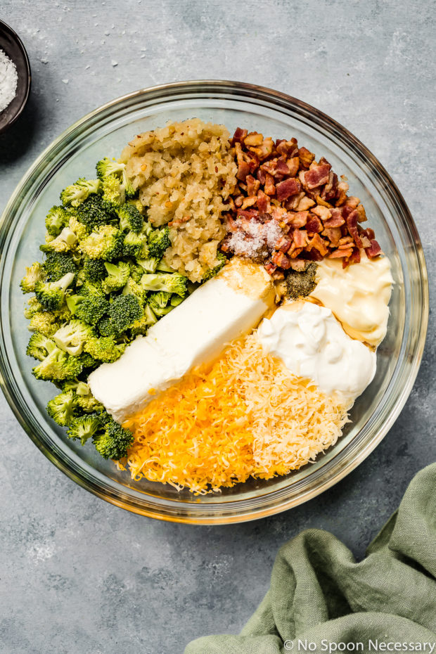 Overhead shot of all the ingredients needed to make Hot Cheesy Bacon Broccoli Dip recipe neatly organized in a large glass bowl before being stirred together - photo of step 4 of the recipe.