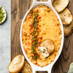 Overhead shot of Hot Cheesy Bacon Broccoli Dip in a white oval baking dish with a slice of toasted baguette inserted into the dip and slices of baguette, a green linen, and ramekins of sliced scallions and salt surrounding the baking dish.
