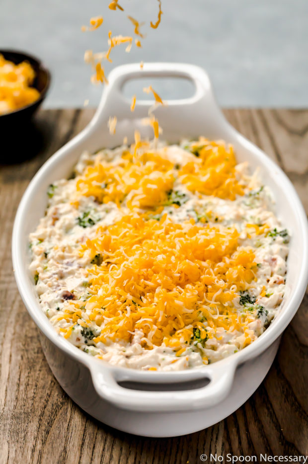 Angled shot of Hot Cheesy Bacon Broccoli Dip in a white oval baking dish with shredded cheese being sprinkled on top and a ramekin of more shredded cheese blurred in the background.