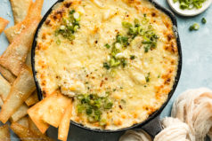 Overhead photo of Hot Crab Rangoon Dip garnished with fresh scallions in a cast iron skillet with a couple wonton chips inserted into the dip and more chips plus a ramekin of sliced scallions next to the skillet.