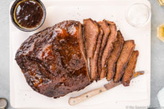 Overhead, landscap shot of Slow Cooker Apricot Bourbon Beef Brisket partially sliced on a white cutting board with a wood handled knife tucked under a few slices of the brisket and a ramekin of sauce and salt next to the brisket.