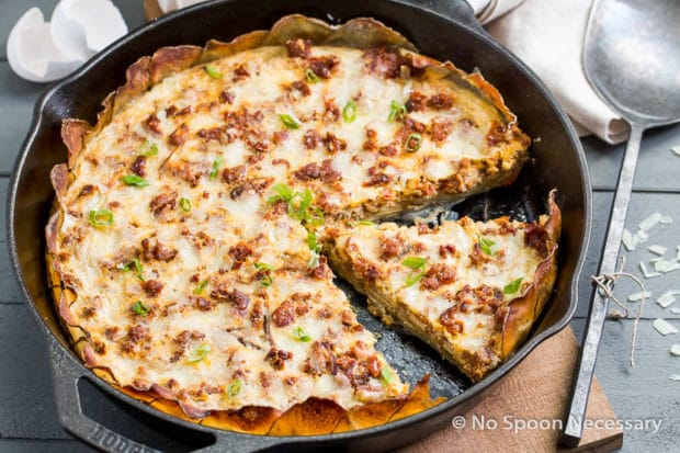 Angled shot of Spanish Potato Crusted Frittata in a cast iron skillet on top of a wood board with a serving spoon and egg shells next to the skillet.
