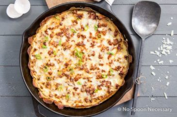 Overhead shot of Spanish Potato Crusted Frittata in a cast iron skillet on top of a wood board with a large serving spoon, grated cheese and egg shells surrounding the skillet.