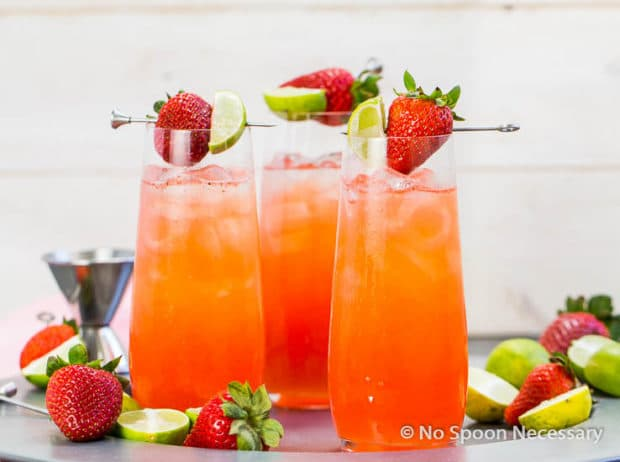 Straight on shot of three Strawberry Key Limeade Cocktails garnished with a fresh strawberry and key lime wedge with fresh strawberries and cut key limes surrounding the cocktails.