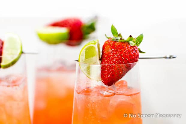 Straight on shot of the top of a Strawberry Key Limeade Cocktail garnished with a fresh strawberry and key lime wedge.