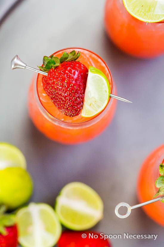 Overhead shot of a Strawberry Key Limeade Cocktail garnished with a fresh strawberry and key lime wedge with additional cocktails, fresh strawberries and cut key limes surrounding the cocktail.