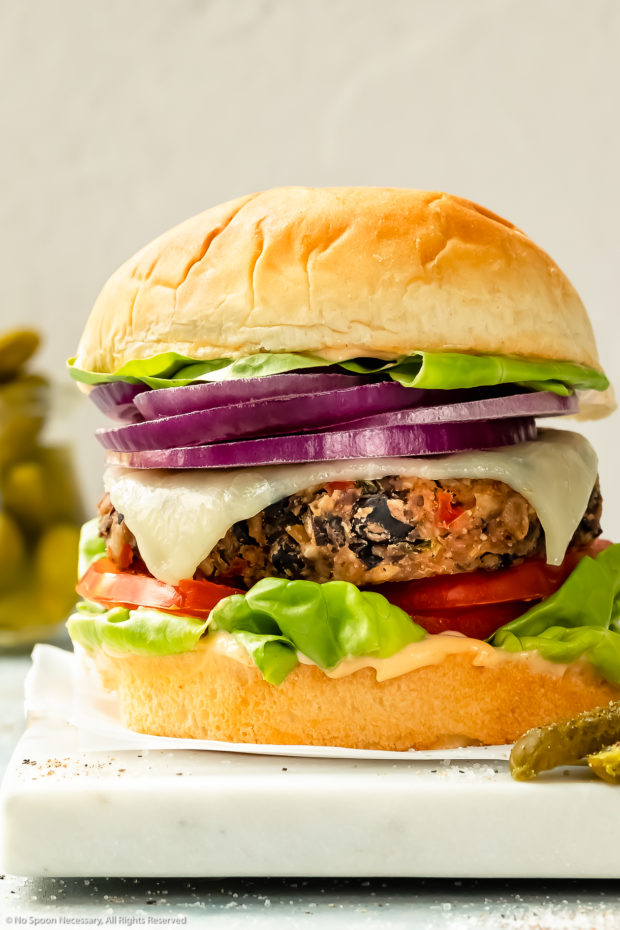 Straight on photo of a veggie cheese burger topped with lettuce, tomato and onion on a white serving board with a jar of pickles blurred behind the burger.