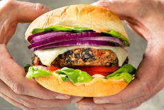 Straight-on, up close photo of two hands holding a black bean burger topped with cheese, lettuce, tomato and onion.