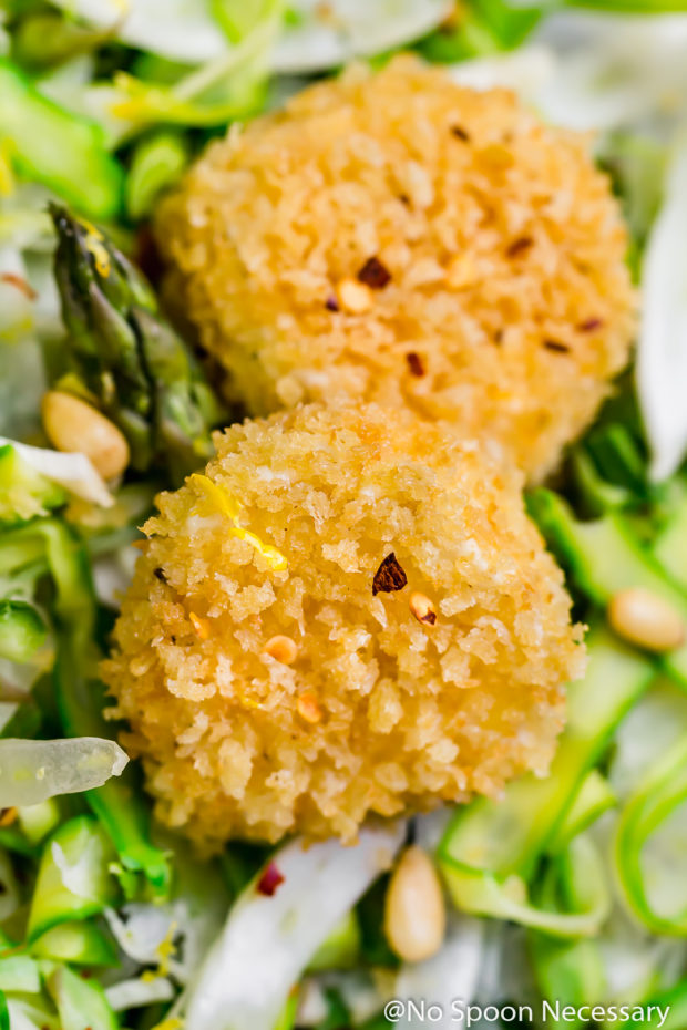Angled, up close shot of panko crusted baked goat cheese - part of a Shaved Asparagus Goat Cheese Salad.