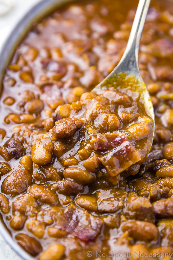Close-up angled shot of Homemade Bacon, Bourbon and Brown Sugar Baked Beans in a galvanized bucket being scooped and served with a spoon
