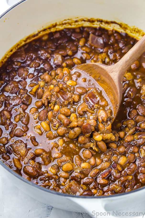 Angled shot of Homemade Bacon, Bourbon and Brown Sugar Baked Beans in a large pot being stirred with a wooden spoon