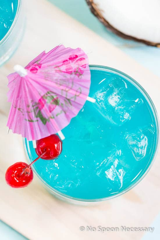 Overhead shot of a rocks glass filled with Rum Blue Island Cocktail and garnished with two cherries and a pink cocktail umbrella.