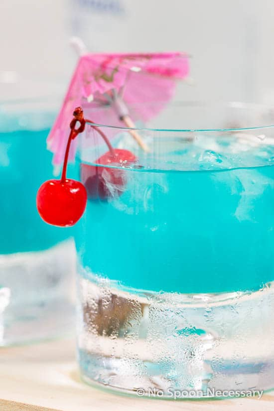 Straight on, up-close shot of a rocks glass filled with Rum Blue Island Cocktail and garnished with two cherries and a pink cocktail umbrella.