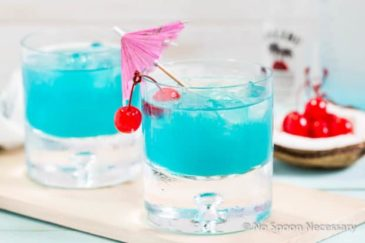 Landscape, straight on shot of a rocks glass filled with Rum Blue Island Cocktail and garnished with two cherries and a pink cocktail umbrella; with an additional cocktail and a coconut holding cherries blurred behind the glass.