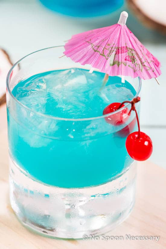 45 degree angle shot of a rocks glass filled with Rum Blue Island Cocktail and garnished with two cherries and a pink cocktail umbrella.