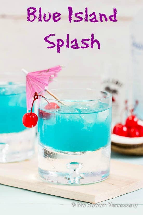 "Straight on shot of a rocks glass filled with Rum Blue Island Cocktail and garnished with two cherries and a pink cocktail umbrella, with the words ""blue island splash"" written on the photo."