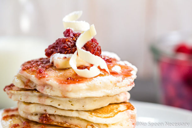 Straight on shot of the top of a stack of macadamia nut pancakes topped with raspberry maple syrup, a pat of butter and curly white chocolate shavings