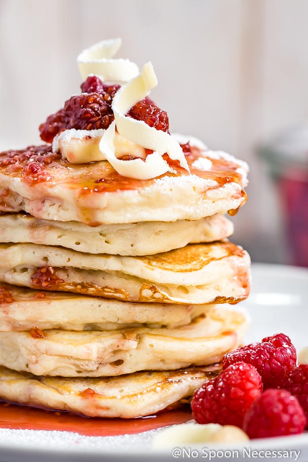 Straight on close up shot of a stack of macadamia nut pancakes dripping in raspberry maple syrup and topped with fresh raspberries, a pat of butter and white chocolate shavings with fresh raspberries blurred in the bottom right corner