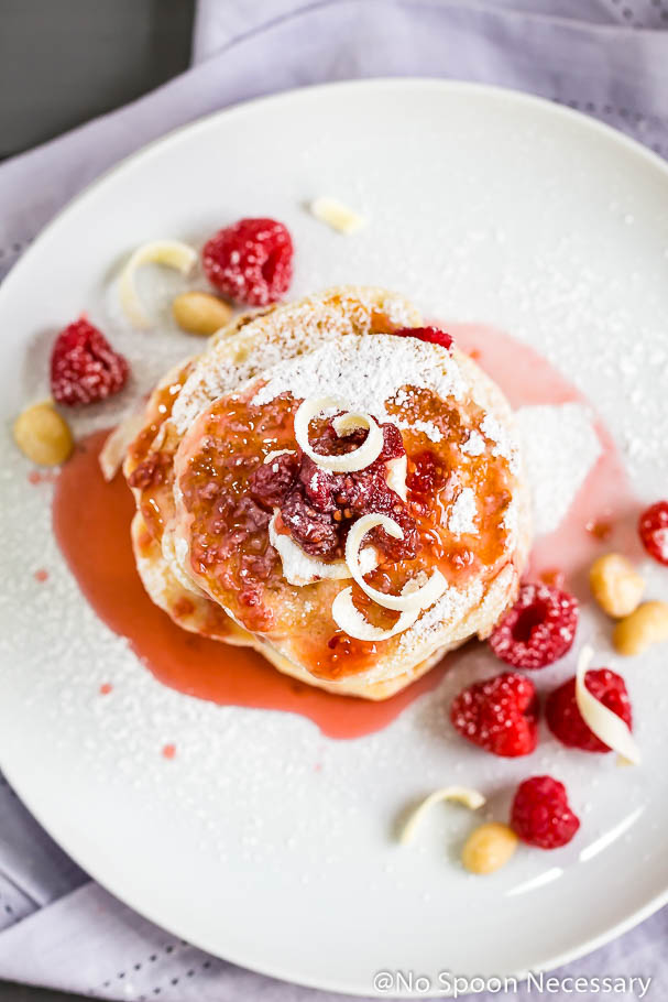 Overhead shot of a stack of macadamia nut pancakes topped with raspberry syrup on a white plate with fresh raspberries and macadamia nuts on the sides and a purple linen underneath the plate