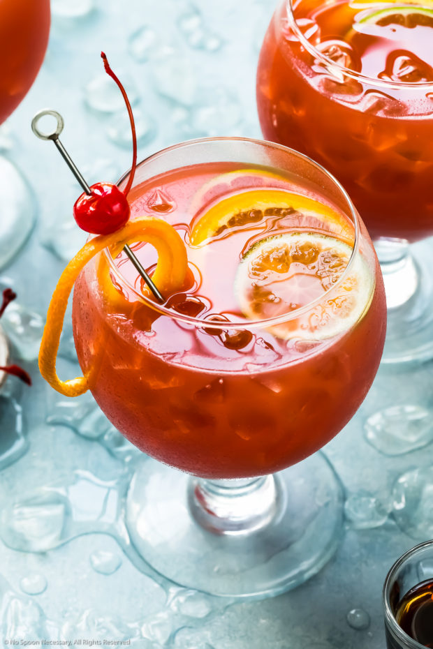 Angled photo of a Rum Runner Cocktail garnished with a maraschino cherry and slices or orange and lime with two additional cocktails barely visible in the background.