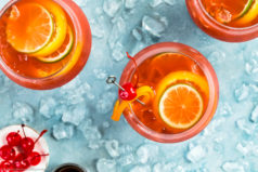 Overhead photo of three Rum Runner cocktails garnished with slices of lime and orange with a ramekin of maraschino cherries and a glass shot glass off to the side of the cocktails.