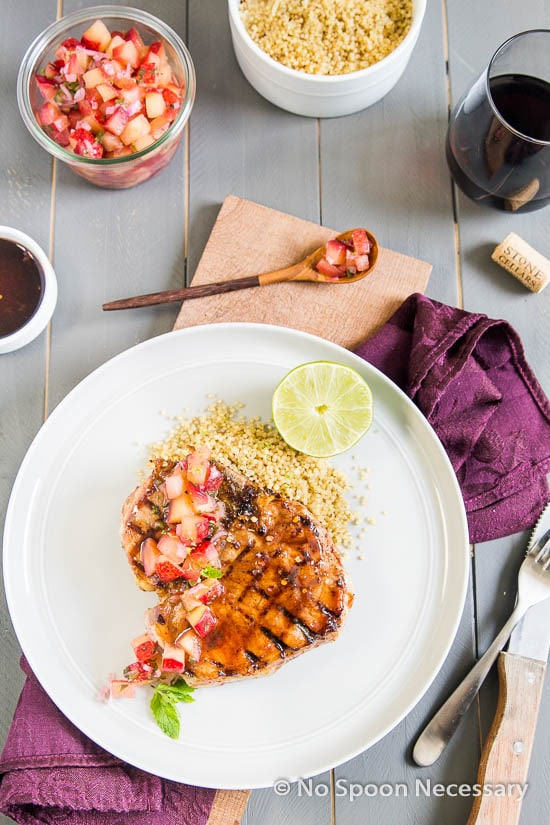 Overhead shot of a Hoisin & Honey Glazed Pork Chop with Plum Salsa on a white plate with couscous and a lime wedge; with a bowl of salsa, bowl of couscous, silverware and red wine glass surrounding the plate.