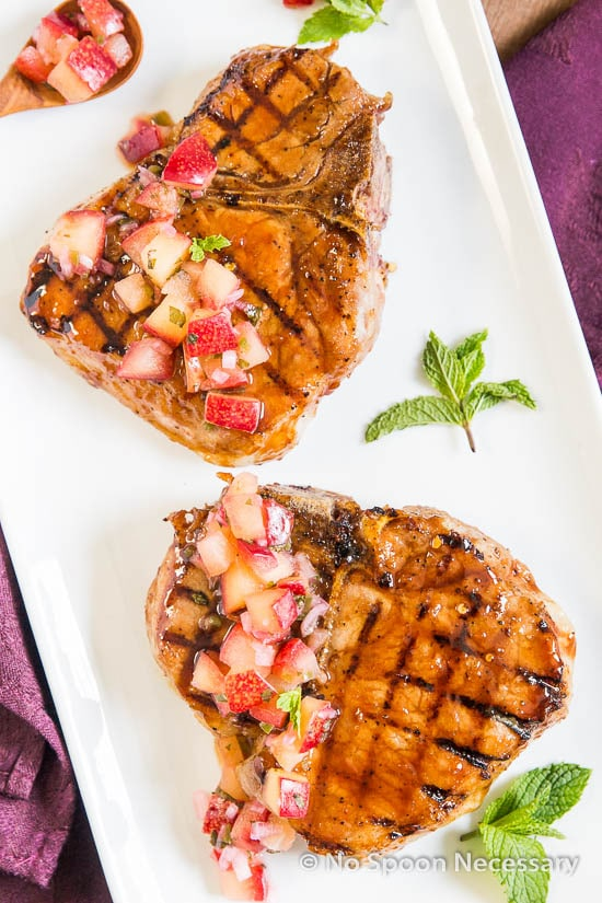 Overhead shot of two Hoisin & Honey Glazed Pork Chops with Plum Salsa on a rectangular white platter with fresh mint.