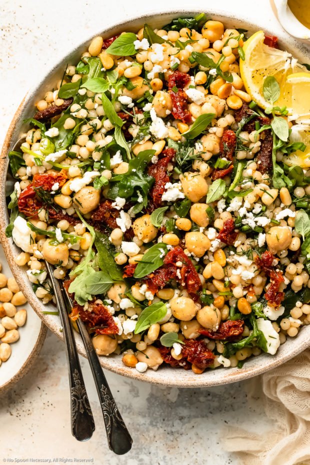 Overhead photo of giant fluffy couscous with sun-dried tomatoes, arugula and chickpeas in a large white bowl with serving spoons inserted under the couscous and a jar of lemon vinaigrette and ramekin of toasted pine nuts next to the bowl.