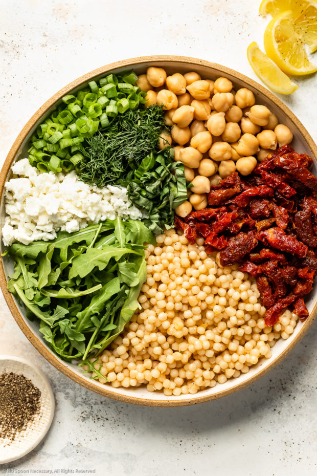 Overhead photo of all the ingredients in Israeli giant couscous neatly organized in a large mixing bowl prior to tossing together.